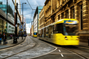 Light rail yellow tram in the city center of Manchester